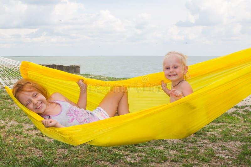 Dwa pięknej rozochoconej dziewczyny w żółtym hamaku zdjęcie stock