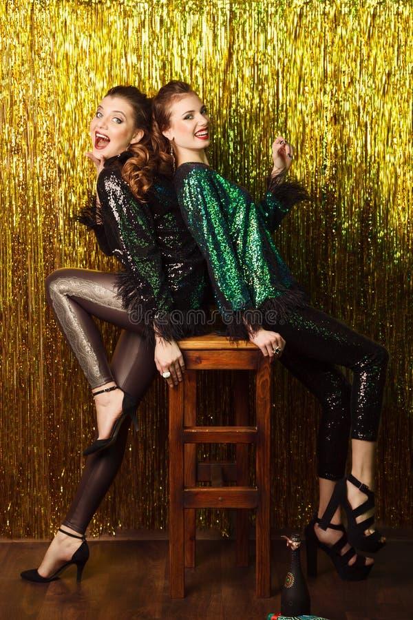 Dwa pięknej rozochoconej kobiety w przyjęciu gwiazdkowym na błyskać bac fotografia royalty free