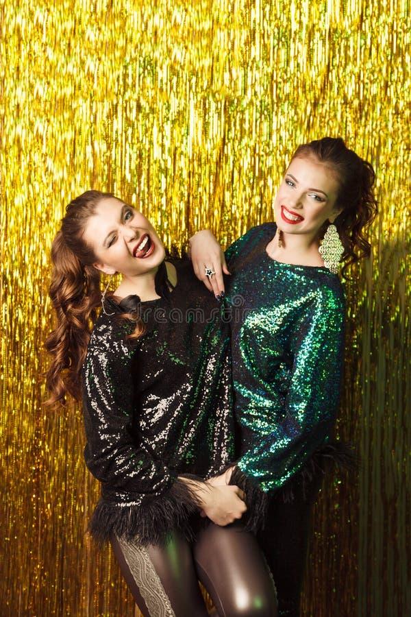 Dwa pięknej rozochoconej kobiety w przyjęciu gwiazdkowym na błyskać bac zdjęcie royalty free