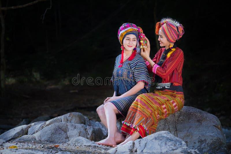 Dwa Pięknej Tajlandzkiej kobiety one uśmiechają się w Karen kostiumu przędzalnianej nici dalej fotografia stock