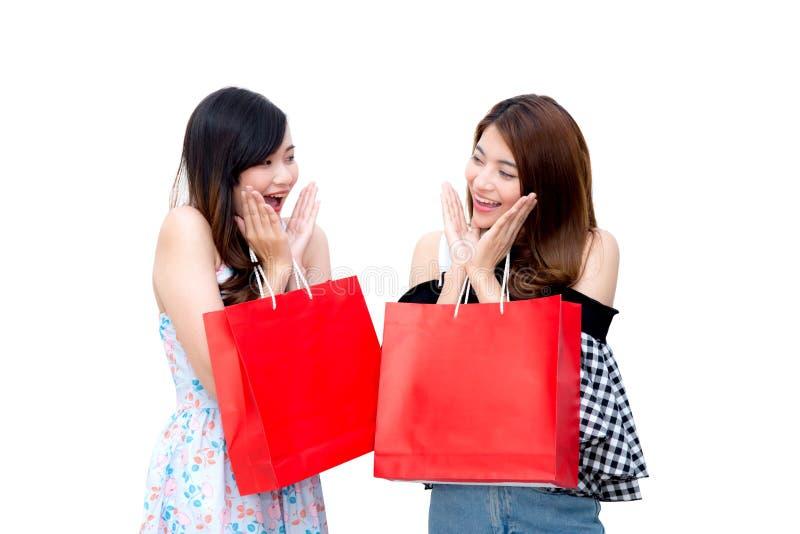 Dwa pięknej uśmiechniętej azjatykciej młodej kobiety z zakupy sprzedaży torbami odizolowywać zdjęcia stock
