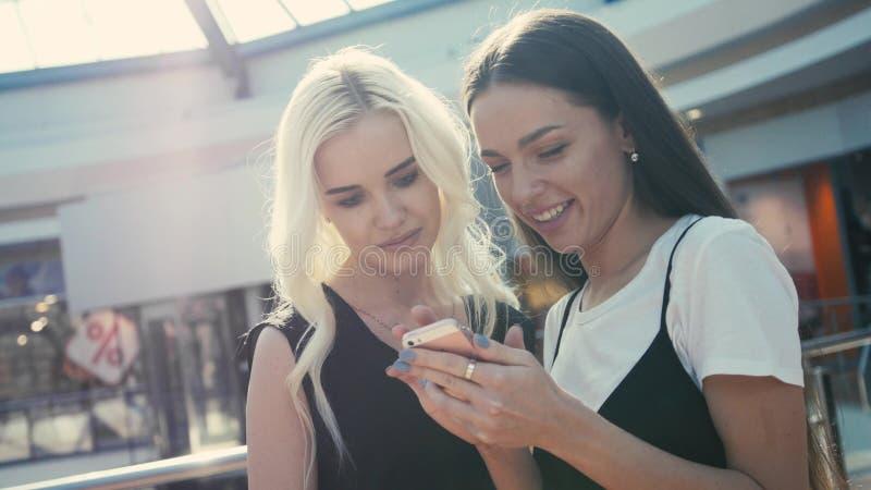 Dwa piękny młody żeński shopaholics surfuje internet w poszukiwaniu rabatów w zakupy centrum handlowym, młode studenckie dziewczy zdjęcia royalty free