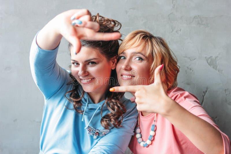Dwa pięknych szczęśliwych młodych kobiet istnego przyjaciela w przypadkowej sukni siedzą blisko betonowej ściany zdjęcie stock