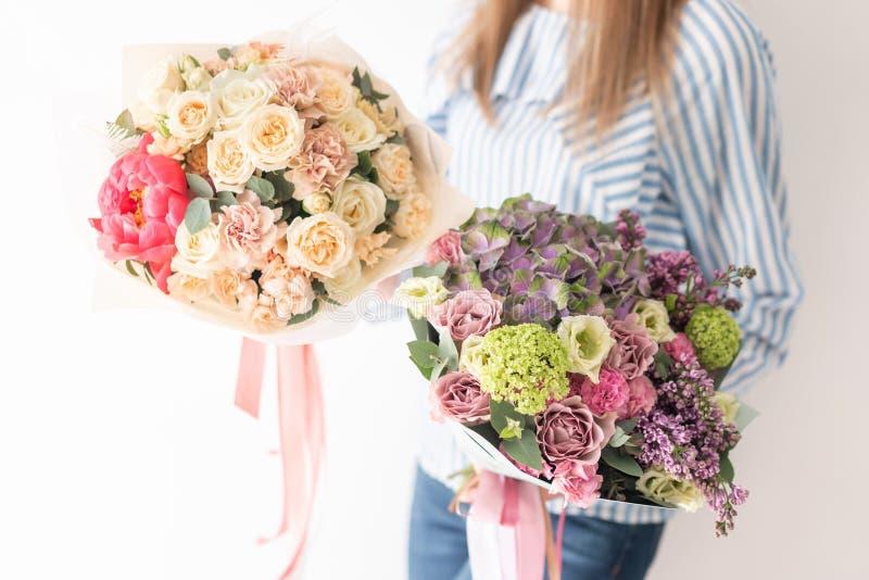 Dwa Pi?knego bukieta mieszani kwiaty w kobiet r?kach praca kwiaciarnia przy kwiatu sklepem Delikatny Pastelowy kolor fotografia stock