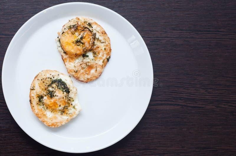 Dwa pieczonego kurczaka jajka z zieleniami na białej tacy na drewnianym stole równie idealnym jak śniadanie obrazy royalty free