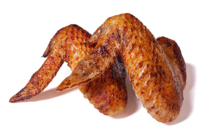 Dwa pieczonego kurczaka skrzydła z crispy skorupą odizolowywającą na bielu fotografia stock