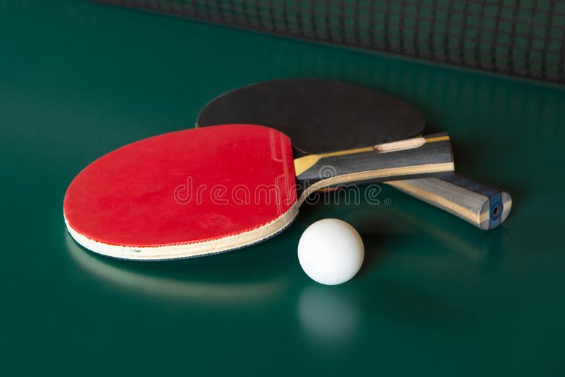 Dwa pingpongowego kanta i pi?ka na zielonym stole Ping-pong sie? fotografia royalty free