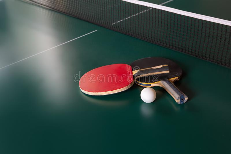 Dwa pingpongowego kanta i pi?ka na zielonym stole Ping-pong sie? fotografia stock
