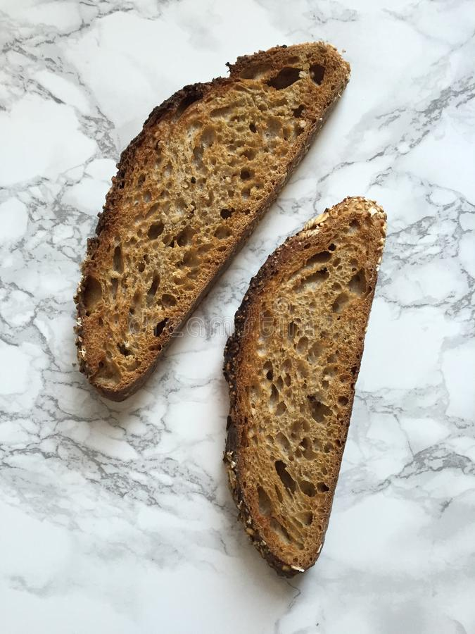 Dwa plasterka artisanal sourdough całej banatki chleb na marmurowym countertop obrazy royalty free