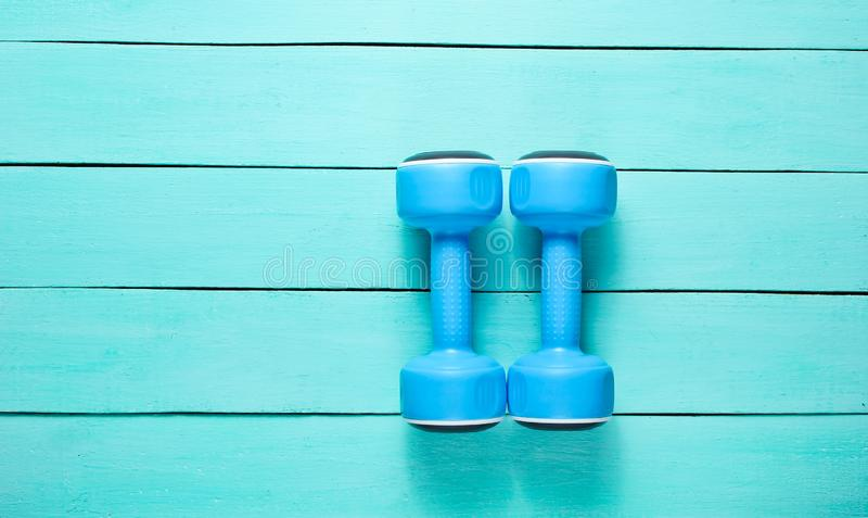 Dwa plastikowego błękitnego dumbbells na błękitnym drewnianym tle zdjęcie royalty free