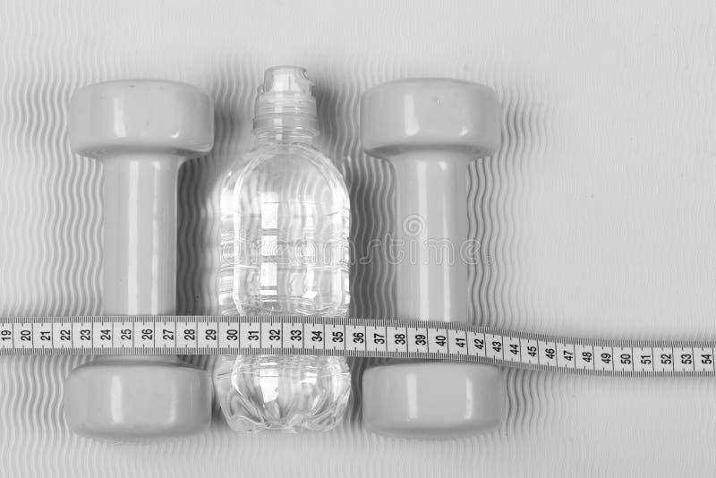 Dwa plastikowej butelki i dumbbells Sporta, dieting i bodybuilding pojęcie, Set ręka ciężar na jaskrawym tle para obraz stock