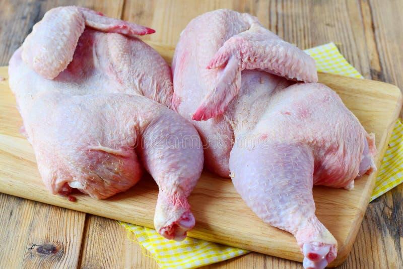 Dwa połówki surowy kurczak na drewnianej tnącej desce Kulinarny krok po kroku jeść zdrowo pojęcia fotografia stock