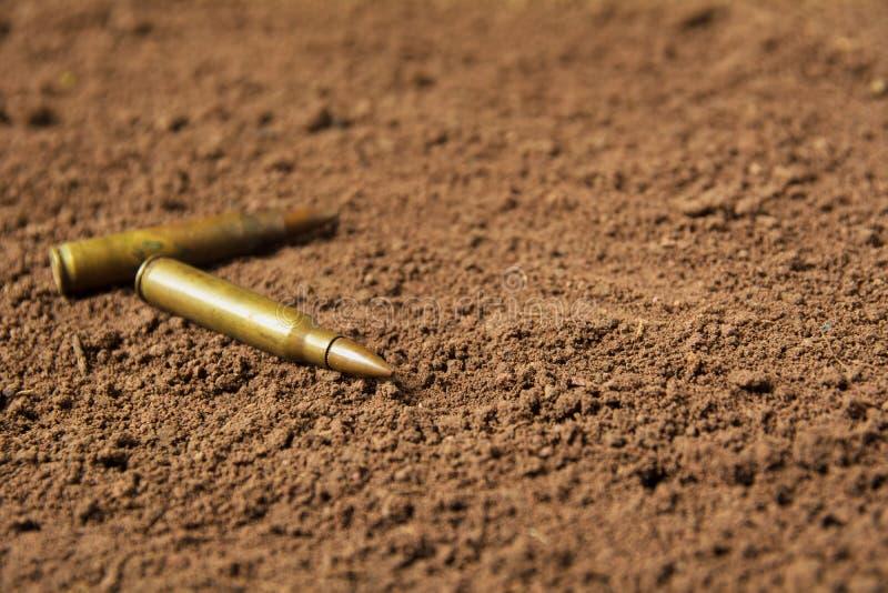 Dwa pociska, maszynowego pistoletu pociski na ziemi fotografia stock