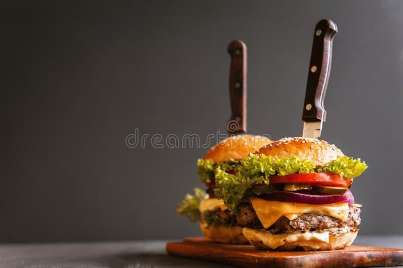 Dwa podlewanie, wyśmienicie domowej roboty hamburger używać siekać wołowinę Na drewnianym stole zdjęcie stock