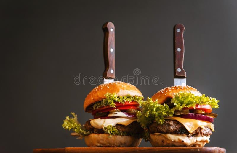 Dwa podlewanie, wyśmienicie domowej roboty hamburger używać siekać wołowinę Na drewnianym stole zdjęcie royalty free
