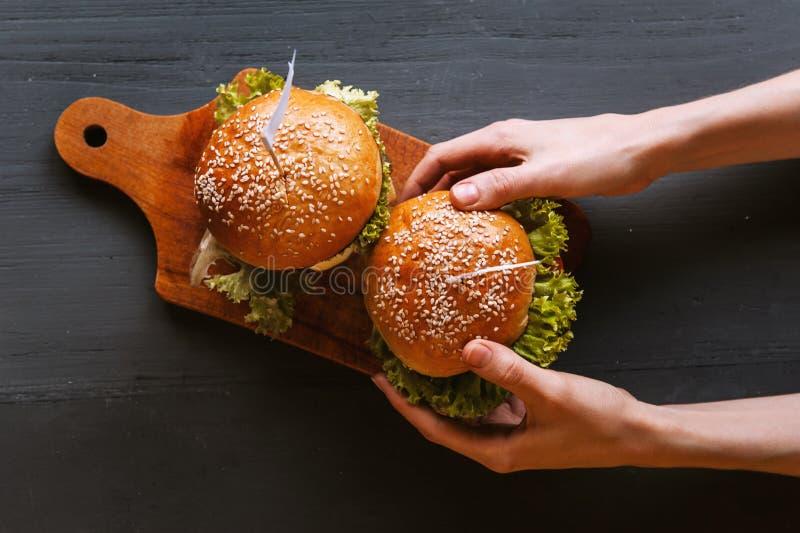 Dwa podlewanie, wyśmienicie domowej roboty hamburger używać siekać wołowinę Na drewnianym stole obraz royalty free