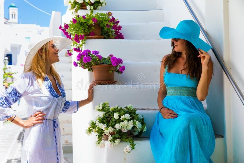 Dwa podróżnicza kobieta cieszy się biel, malownicze aleje Cyclades wyspy w Grecja fotografia royalty free