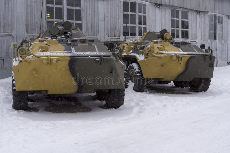 Dwa pojazdów pancernych stojak przy hangarem na zima dniu zdjęcie stock