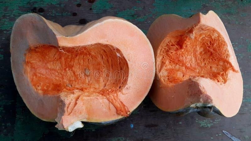 Dwa pomarańczowego plasterka dojrzała bania na starym drewnianym stole obrazy stock