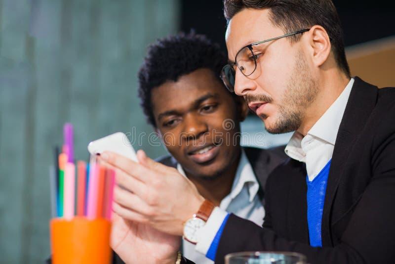 Dwa pomyślnego biznesmena przy biurowego zegarka mobilnym mądrze telefonem obraz stock