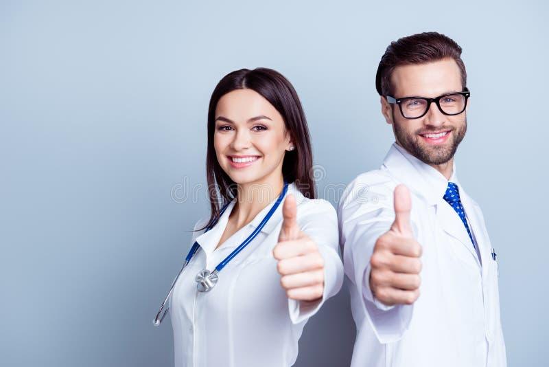 Dwa pomyślnej lekarki w mundurze wpólnie pokazuje aprobaty dalej zdjęcie royalty free
