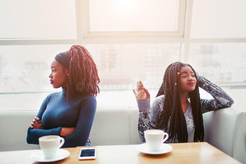 Dwa potomstw afrykańska kobieta szalenie na each inny Siedzą saparately na jeden łóżku Modele patrzeją w różnych kierunkach obraz stock