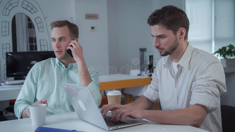 Dwa potomstw biznesmen pracuje przy nowożytnym biurem zdjęcie royalty free