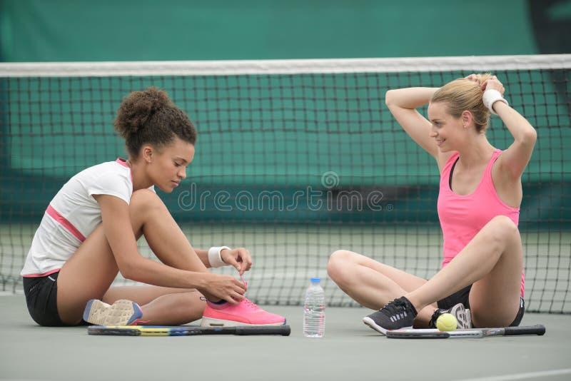 Dwa potomstw tenisowy żeński obsiadanie na podłoga obrazy royalty free