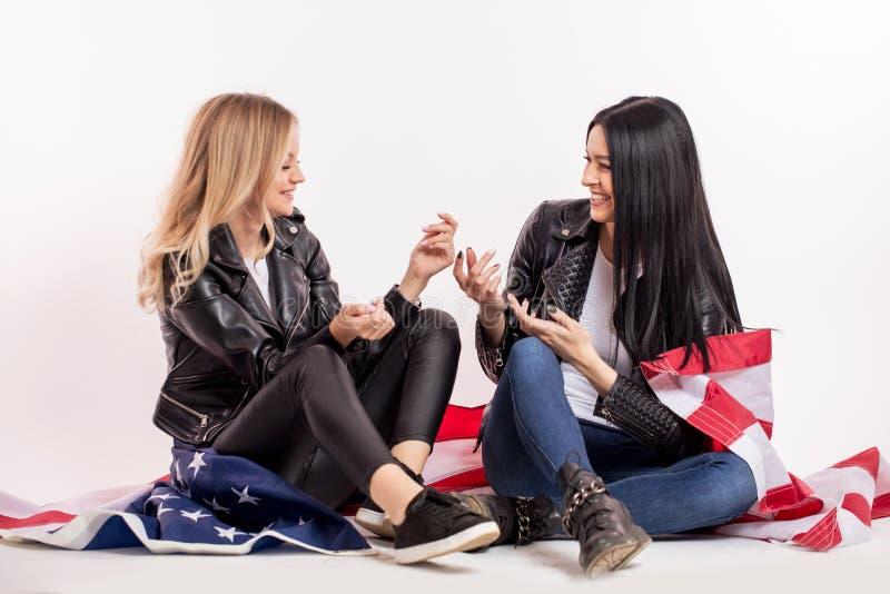 Dwa pozytywnej dobrej przyglądającej dziewczyny mają zabawę podczas gdy siedzący na flaga fotografia royalty free