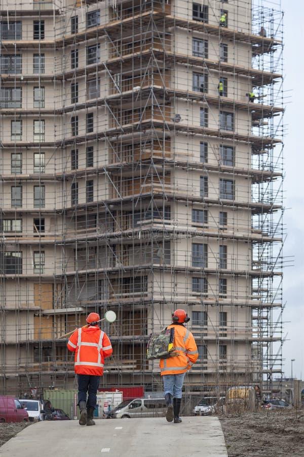 Dwa pracowników budowlanych spacer plac budowy obrazy stock