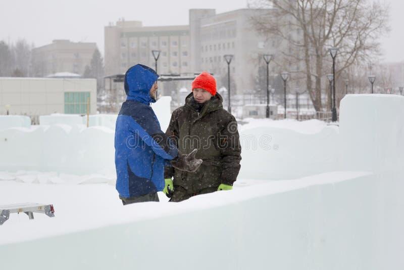 Dwa pracowników rozmowa na zgromadzenie miejscu zdjęcia royalty free