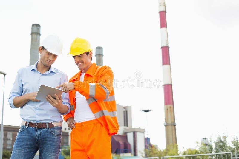 Dwa pracownika budowlanego dyskutuje nad pastylka pecetem przy przemysłem zdjęcia stock
