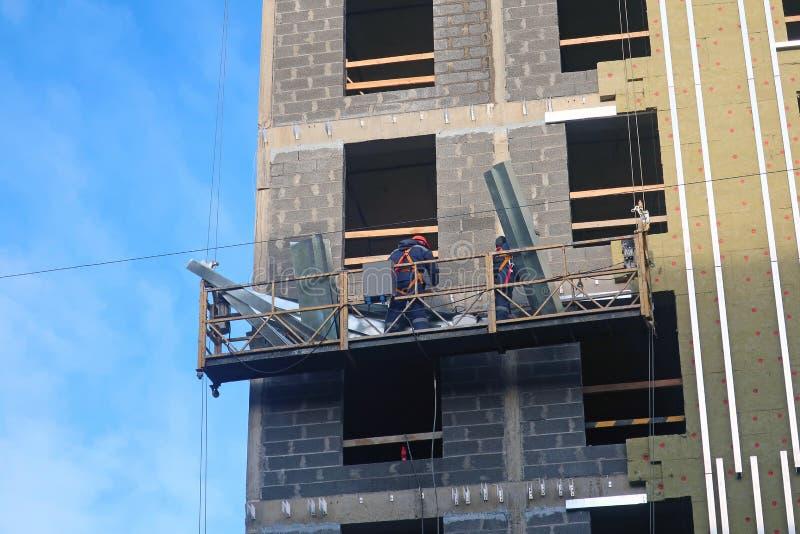 Dwa pracownika instalują izolację na ścianie obraz stock