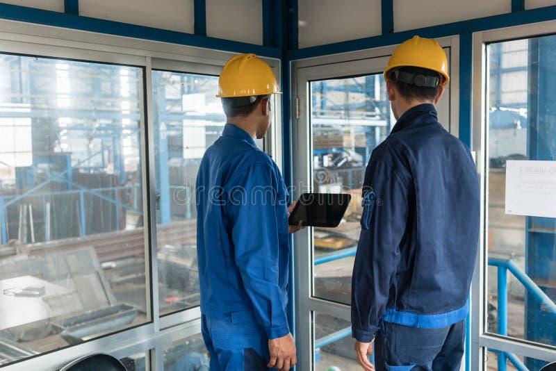 Dwa pracownika jest ubranym ciężkich kapelusze podczas gdy używać pastylka peceta zdjęcia stock