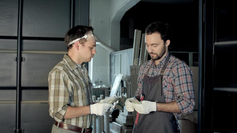 Dwa pracownika liczą pieniądze w warsztacie fotografia royalty free