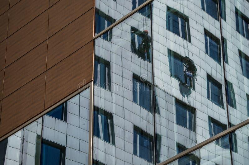 Dwa pracownika myją okno na wieżowu fotografia royalty free