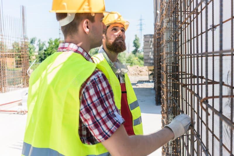 Dwa pracownika sprawdza trwałość stalowa struktura obrazy stock