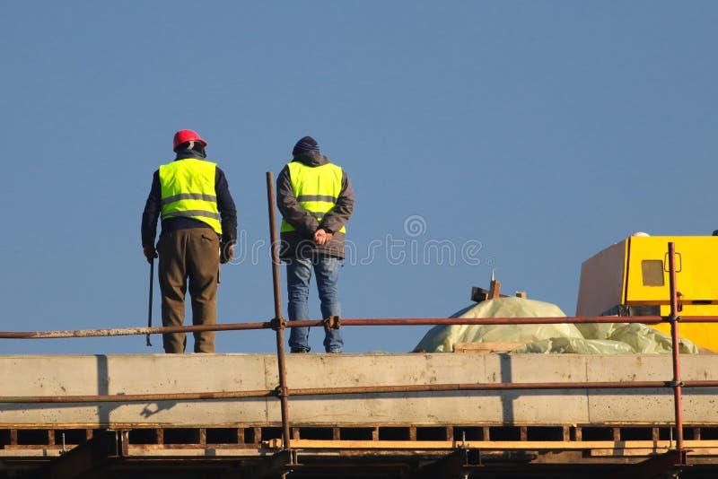 Dwa pracownika w kolorze żółtym przy budowy ower niebieskim niebem obrazy royalty free