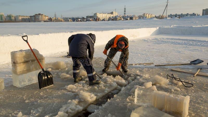 Dwa pracownika w kombinezonach usuwają lód od dziury obraz royalty free