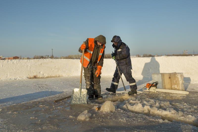 Dwa pracownika w kombinezonach usuwają lód od dziury zdjęcie stock