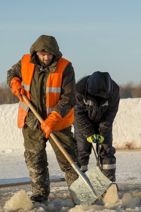 Dwa pracownika w kombinezonach usuwają lód od dziury zdjęcia royalty free