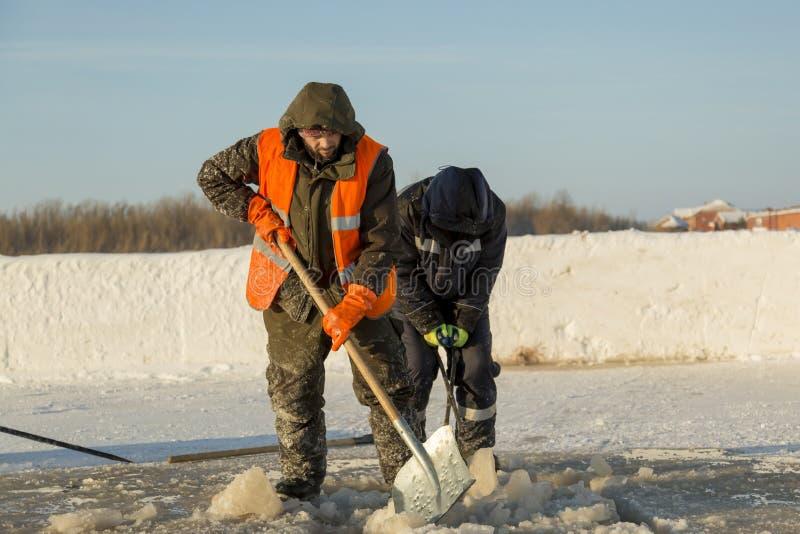 Dwa pracownika w kombinezonach usuwają lód od dziury obraz stock