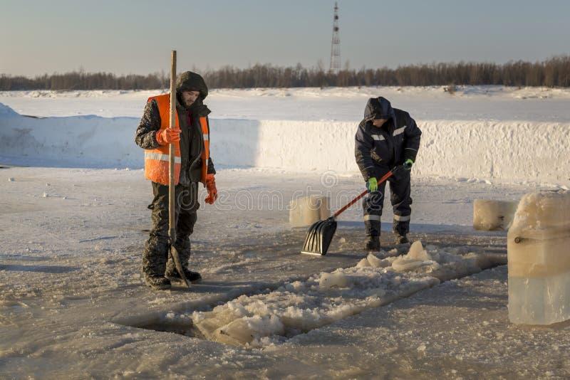 Dwa pracownika w kombinezonach usuwają lód od dziury obrazy stock