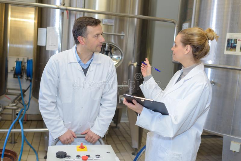 Dwa pracownika w labcoat pracuje przy fabryką fotografia stock