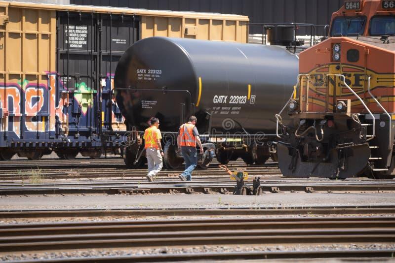 Dwa pracownika zbliżają się platformę dla transportu ciecze tak jak olej napędowy lub ropa naftowa zdjęcie royalty free