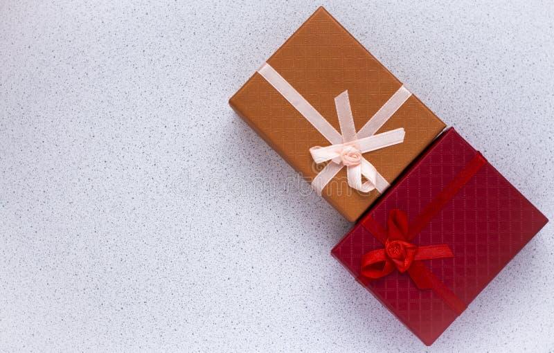 Dwa prezenta pudełka w czerwieni i pomarańcze, z łękami na białym tle z kopii przestrzenią fotografia stock
