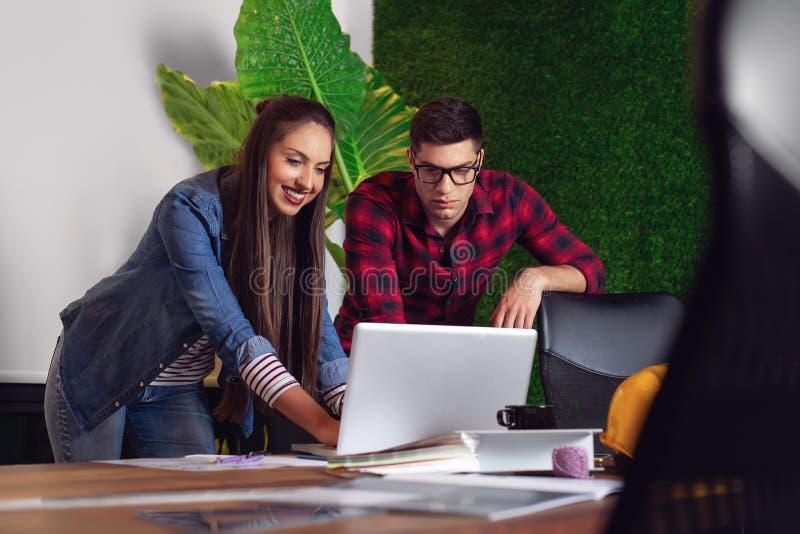 Dwa projektanta architekta pracuje wraz z laptopu obsiadaniem przy stołem zdjęcie royalty free