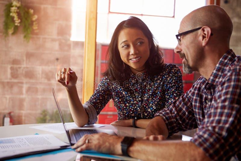Dwa projektanta Z laptopu spotkaniem W Nowożytnym biurze obraz stock