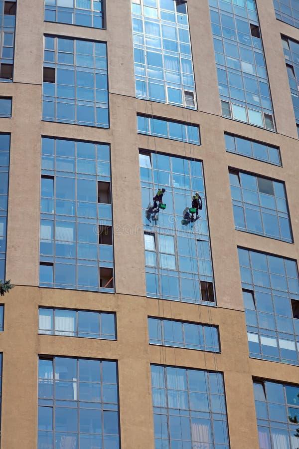 Dwa przemysłowego arywisty myją okno w wysokim budynku zdjęcie royalty free