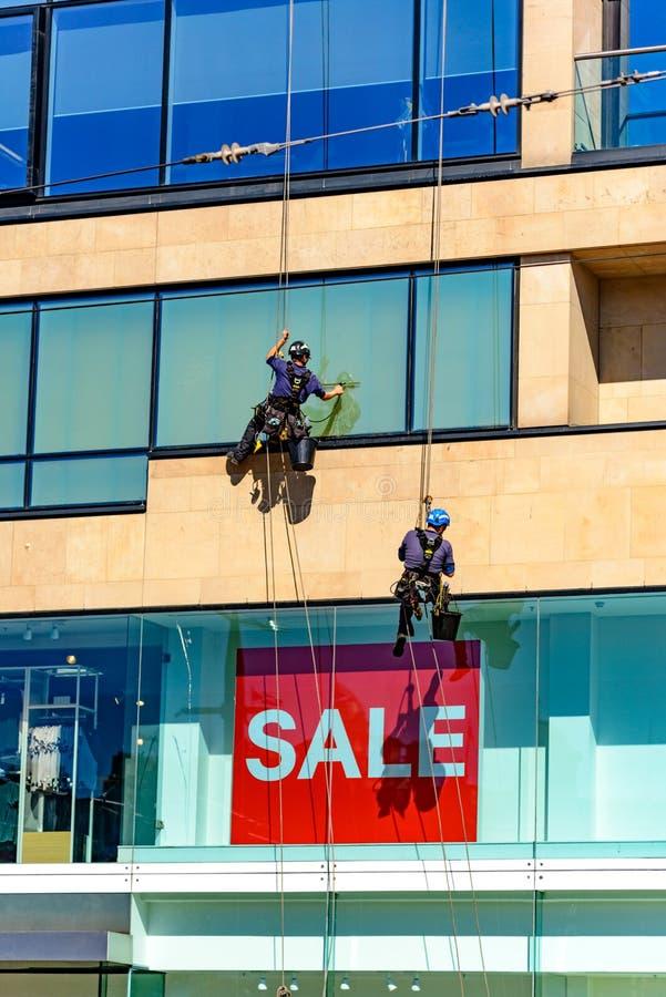 Dwa przemysłowego nadokiennego czyściciela na wysokim budynku zdjęcia royalty free